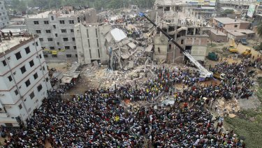 People gather as rescuers look for survivors at the site of the Rana Plaza collapse.