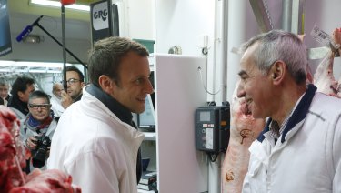 Then French presidential candidate Emmanuel Macron, left, shakes hands with a butcher as he visits the meat pavillion at the Rungis wholesale food market, south of Paris, in May 2017.