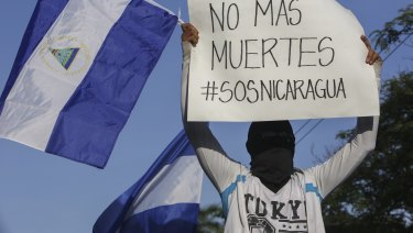 "A masked demonstrator holds a Nicaraguan flag and a sign with a message that reads in Spanish: ""No more deaths""."