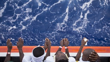 """African migrants stand on the deck of the Aquarius vessel of the """"SOS Mediterranee"""" and MSF (Doctors Without Borders)  in August."""