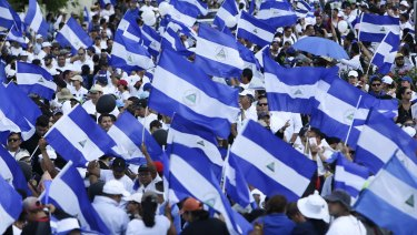 Demonstrators protesting government repression wave Nicaraguan flags in Managua.