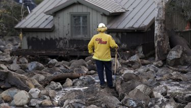 A firefighter walks among the rocks and mud left by a mudslide  in Montecito, California.