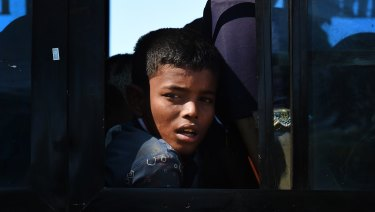 A Rohingya refugee boy peers out the window of a bus that will take the newly arrived refugees to camps in Bangladesh.