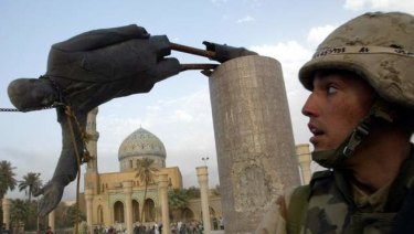 A US soldier watches as a statue of Iraq's President Saddam Hussein falls in central Baghdad in 2003.