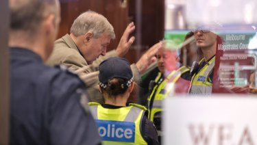 Cardinal George Pell goes through security at Melbourne Magistrates Court on Monday morning.