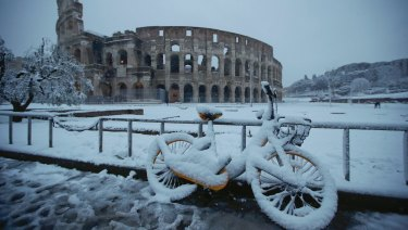 A bicycle is parked in front the ancient Colosseum during a snowfall in Rome.