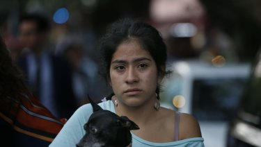 A woman holds her dog in the aftermath of a 7.2-magnitude earthquake that shook Mexico City.