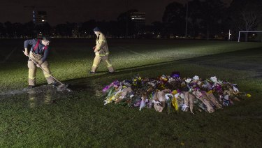 Firefighters clean graffiti painted at the memorial site of comedian Eurydice Dixon.