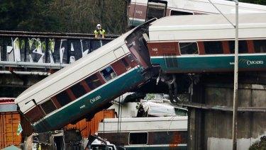 An investigator takes photos off a railroad bridge at the scene of where an Amtrak train derailed in DuPont, Washington..