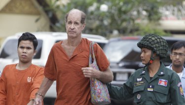 Australian filmmaker James Ricketson is escorted by prison guards while walking at the Cambodian Supreme Court in Phnom Penh.