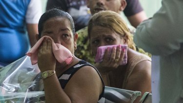 Grieving relatives of passengers who perished in Cuba's worst aviation disaster wait for the identification of the bodies at the morgue in Havana.