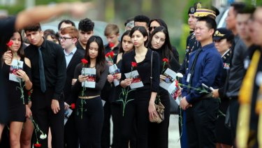Mourners hold flowers during the funeral for Peter Wang, who was killed at Marjory Stoneman Douglas High School.