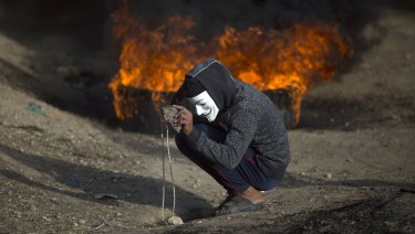 A Palestinian protester prepares a stone to hurl at Israeli troops during a protest at the Gaza Strip's border with Israel on Friday, as protests continued, albeit it with fewer people.
