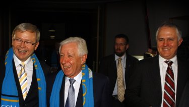 Then PM Kevin Rudd wears a Come Play! scarf with Frank Lowy and then Opposition Leader Malcolm Turnbull in June 2009.