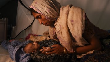 Laila Begum holds her son Mohammed Ifran's hand as he receives treatment at the Red Cross Field Hospital in Kutupalong refugee camp, Cox's Bazar, Bangladesh in November.