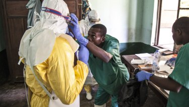 Health workers don protective clothing as they prepare to attend to patients in the isolation ward to diagnose and treat suspected Ebola patients, at Bikoro Hospital in Bikoro.