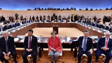 From left:  US President Donald Trump, China's Xi Jinping, Angela Merkel, Argentinian President Mauricio Macri and Prime Minister Malcolm Turnbull turn around for photographers at the G20 meeting in Hamburg in July.