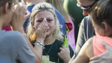 A woman wipes away tears during a prayer vigil following a shooting at Santa Fe High School in Santa Fe, Texa.