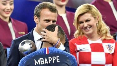 French president Emmanuel Macron kisses Kylian Mbappe.