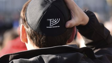 A man wears a Jewish skullcap, or kippa, as he attends a demonstration against anti-Semitism  in Cologne.