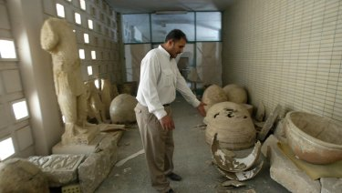 An Iraqi guard among the smashed remains of ceramic jars at Baghdad's biggest archaeological museum.