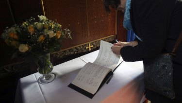 Members of the public sign a book of condolence at Gonville and Caius College.