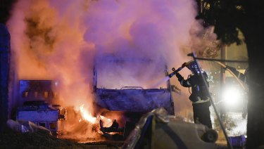A firefighter works to extinguish a burning vehicle in Nantes on Tuesday.
