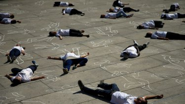 Activists lay on the ground to mark World Refugee Day during a protest in Madrid.