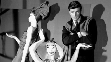 Hubert de Givenchy poses with mannequins in his shop in Paris in 1952.