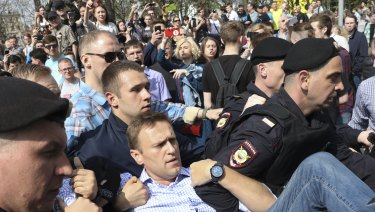 Russian police carrying struggling opposition leader Alexei Navalny, centre, at a demonstration against President Vladimir Putin in Pushkin Square in Moscow on Saturday.
