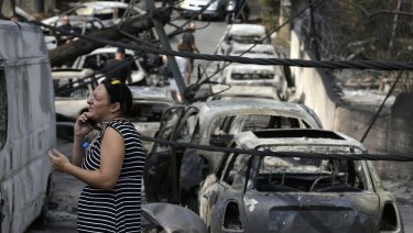 A woman stands amid the charred remains of burned-out cars in Mati.