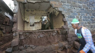 A man walks past a house damaged by the dam flooding, near Solai, in Kenya's Rift Valley.