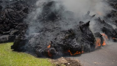 Lava creeps across the road in the Leilani Estates in Pahoa, Hawaii.