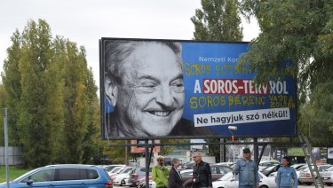 Egyutt (Together) opposition party stand in front of billboards of the government's campaign against George Soros and his support for migration in Budapest.