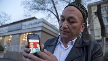 Omir Bekali holds up a mobile phone showing a photo of his parents. He believes they have been detained in China.