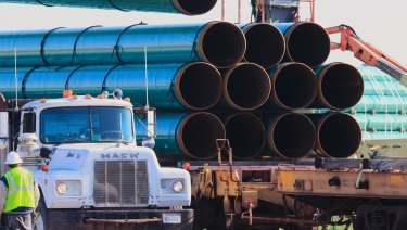 Workers unload pipes for the proposed Dakota Access oil pipeline.