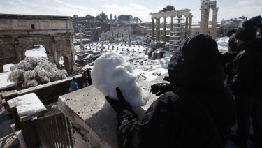 Sculptor Francesca Antonello moulds snow into a face as people look out towards the ancient Roman Forum covered in white.