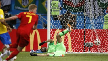 Brazil goalkeeper Alisson sits on the pitch after Belgium's Kevin De Bruyne scores his side's second goal.