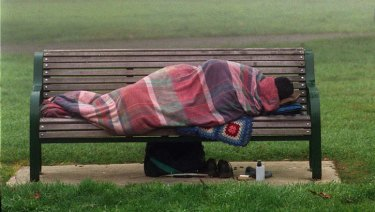 A homeless person lies bundled on a park bench.