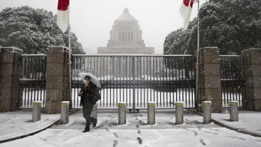 Snow falls as a man holding an umbrella walks past the main gate to the National Diet building in Tokyo.