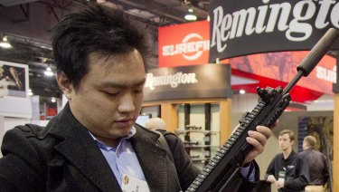 Kevin Kao, of Irvine, California, examines a military grade Remington Adaptive Combat Rifle at the 35th annual SHOT Show in Las Vegas.