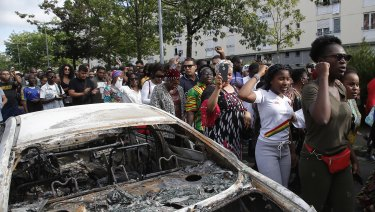 People walk past a charred car during a march after police shot of a driver.