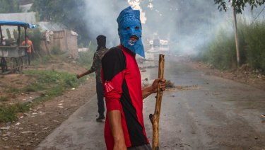 A masked villager holds a wooden stick and stones during a protest south of Srinagar, Indian-controlled Kashmir.