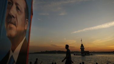 Backdropped by the Bosporus Strait separating Asia and Europe, a man strolls past an election poster of President Recep Tayyip Erdogan, in Istanbul.
