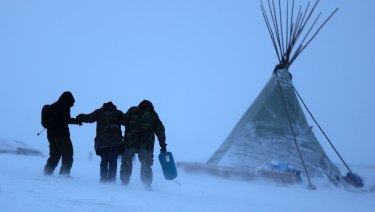 People walk along a snowy hillside in a storm at the Oceti Sakowin camp where people have gathered to protest the Dakota Access oil pipeline in Cannon Ball, ND.