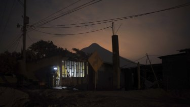 """A journalist stands in the doorway of a home, evacuated by its inhabitants near the """"Volcano of Fire,"""" in Escuintla, Guatemala,"""