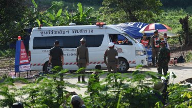 An ambulance carrying the 5th person to be rescued from Tham Luang cave drives past the caves park entrance.