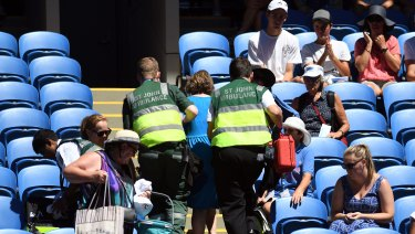A spectator is treated by ambulance officials in soaring heat at the Australian Open on Thursday, January 18.