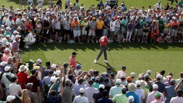Tigermania: Tiger Woods hits his tee shot in front of a huge crowd during practice.
