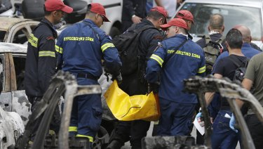 Firefighters remove a dead body in Mati, east of Athens.